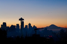 Seattle Space Needle with Christmas tree lights and Mt Rainier at sunrise